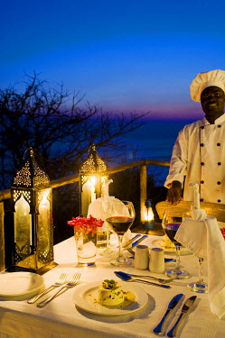 MW1368 Malawi, Lake Malawi National Park.  A chef stands by dinner table on the veranda of one of the chalets at Pumulani Lodge with Lake Malawi behind.