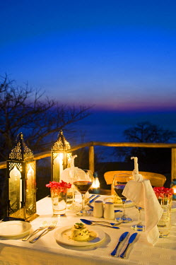 MW1369 Malawi, Lake Malawi National Park.  Dinner laid on the veranda of one of the chalets at Pumulani Lodge with Lake Malawi behind.