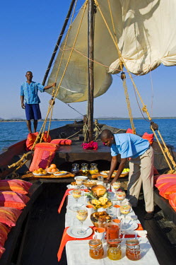 MW1393 Malawi, Lake Malawi National Park.  A lavish breakfast is laid out for guests on board Pumulani's traditional dhow in readiness for a morning cruise.