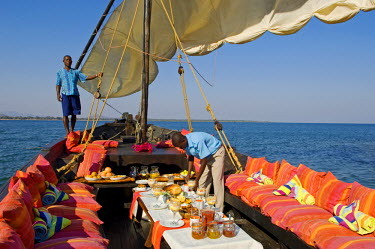 MW1394 Malawi, Lake Malawi National Park.  A lavish breakfast is laid out for guests on board Pumulani's traditional dhow in readiness for a morning cruise.