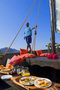 MW1398 Malawi, Lake Malawi National Park.  A lavish breakfast is laid out for guests on board Pumulani's traditional dhow in readiness for a morning cruise.