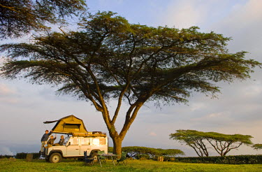 MW1461 Malawi, Thyolo.  Camping overland style with a roof tent fitted to a safari landrover beneath majestic Acacia abyssinica trees at a tea plantation.  (MR)