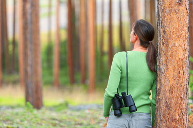 NOR0534AW Norway, Woman leaning against tree with binoculars (MR)
