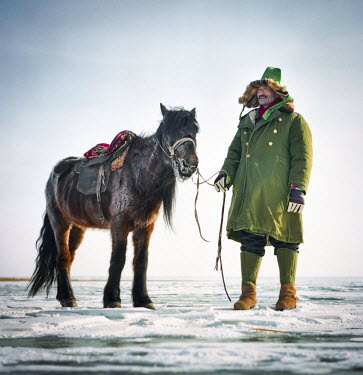 AR4281100011 An indigenous Kazakh herder stands with his horse on Wulun Guhu Lake in Xinjiang,  China