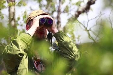 NP05951410 Man with binoculars, Arjeplog, Sweden