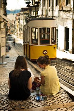 POR6620AW Portugal, Distrito de Lisboa, Lisbon, Bairro Alto, two young girl painting the tram of elevador da Bica,