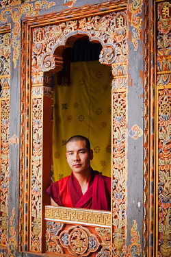 Young monk looking through one of the beautiful carved window frames at Tango Monastery.