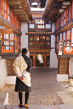 A man at Jakar Dzong wearing a silk shawl known as a kabney over his gho, the national dress for Bhutanese men.