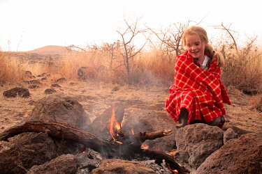 KEN7649 Girl next to safari campfire in Elerai Conservancy, near Amboseli National Park, Kenya.