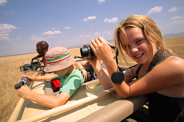 KEN7674 Children photographing wildlife from the open roof of a safari vehicle in the Masai Mara National Reserve, Kenya.
