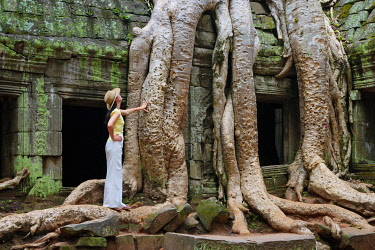 CMB1211AW Cambodia, Angkor, Siem Reap, Ta Prohm Temple, Woman exploring MR