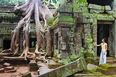CMB1213AW Cambodia, Angkor, Siem Reap, Ta Prohm Temple, Woman exploring MR