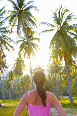 MAY0213AW Malaysia, Langkawi, Woman infront of palm trees MR