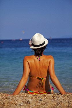 CRO1161 Croatia, Brac Island, Central Europe. Young woman sunbathing at Zlatni Rat beach  in Bol. MR