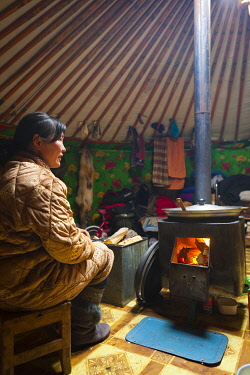 MON1250AW Mongolia, Ovorkhangai, Orkhon Valley. A Nomad woman sits by the fire inside the family ger.
