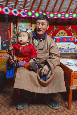 MON1261AW Mongolia, Ovorkhangai, Khungu Khan Natural Reserve. A Nomad man sits inside his ger with his daughter.