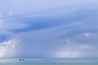 SIL0002AW Africa, Sierra Leone, Southern Province, Turtle Islands. A man rows a boat while a rain storm approaches.