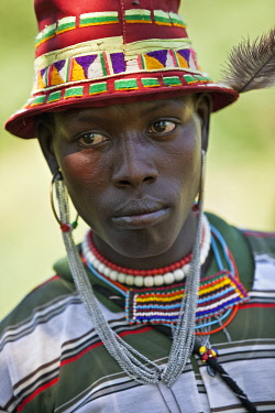 KEN7808 A Pokot warrior attending a Sapana ceremony, wears an interesting mixture of modern dress with traditional ornaments.
