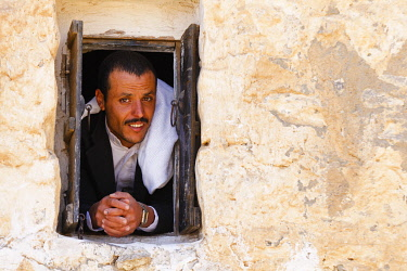 YEM0231AW Yemen, Sana'a Province, Haraz Mountains, Al Hajjarah. A man looks out from a window.