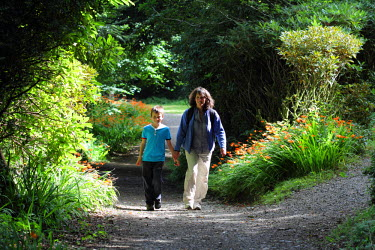 WAL7380 Mother and son walking along a path at the National Trust's Colby Woodland Garden, near Amroth, Pembrokeshire, Wales