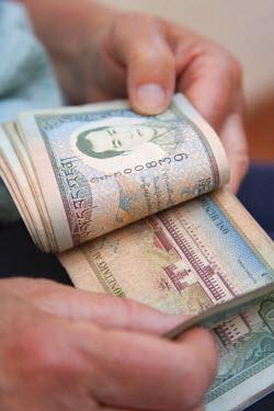 AS04_KSU0263_M Hands counting Bhutanese currency, Bhutan