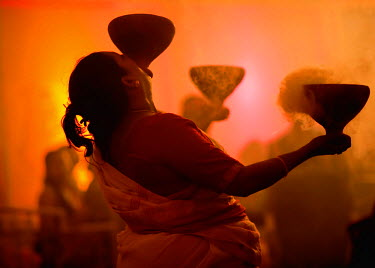 Dhunuchi folk dance performed at Durga Puja festival in Bengal, India. Burning embers of coal are placed in a pot and devotees of the goddess carry 1 - 3 pots as they dance to the unique beat of drumm...