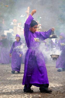 SA10_BBI0004_M Central America. Guatemala. Antigua Guatemala. A young boy in traditional Semana Santa purple robe holding a incense burner during the procession of Semana Santa Holy Week