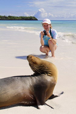 ECU1193 Girl photographing sea lion, Gardner Bay, Espanola, Galapagos Islands, Ecuador