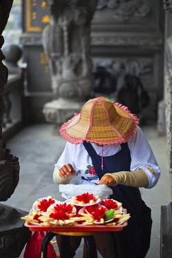 TW01092 Taiwan, Taipei, Guandu, Woman selling flower offerings at Guandu Temple