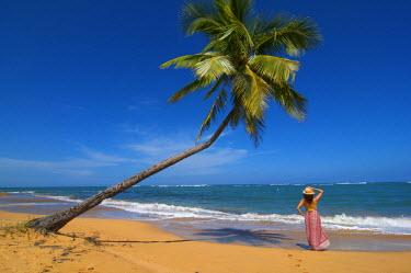 PUR0022AW Woman relaxing on beach, Palmas de Mar, Puerto Rico (MR)