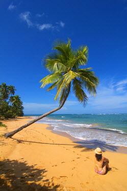 PUR0020AW Woman relaxing on beach, Palmas de Mar, Puerto Rico (MR)