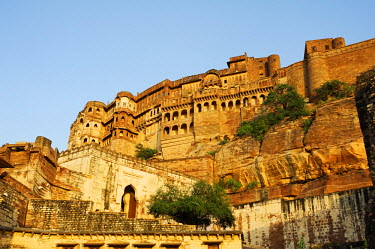 IND6910 India, Rajasthan, Jodhpur. Perched atop a sheer rocky bluff, the main palace buildings of Mehrangarh Fort are guarded by a muscular arrangement of fortifying walls and gateways.