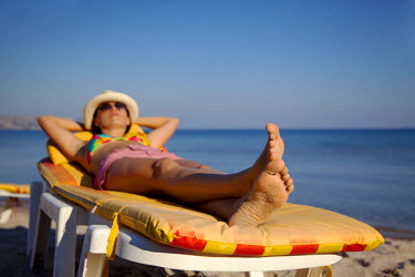 GRE0502 Greece, Kos, Southern Europe, Young woman sunbathing in Paradise bay. MR