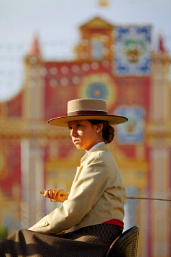 SPA4420 Seville, Andalusia, Spain, A young woman dressed in traditional horse riding clothes in front of the main gate of the Feria de Abril