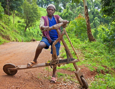 UGA1327 A proud young boy with his homemade wooden bicycle, Uganda, Africa