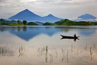 UGA1331 A woman paddles a dugout canoe across Lake Mutanda with its stunning backdrop of the Virunga Volcanoes, Uganda, Africa