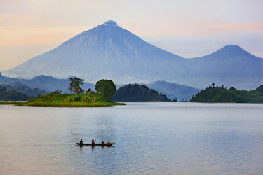 A man and woman paddle a dugout canoe across Lake Mutanda at sunrise. This lake with its many small islands has a stunning backdrop of the Virunga Volcanoes, Uganda, Africa