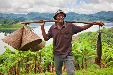 UGA1337 A jovial fisherman with fishing baskets and his catch of the day, which he caught in Lake Mutanda, Uganda, Africa