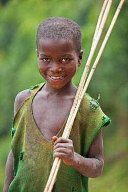 UGA1340 A happy young boy with his homemade fishing rods in hand, Uganda, Africa