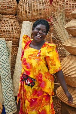 UGA1373 A happy Muganda woman selling baskets and woven mats at a stall by the side of the road, Uganda, Africa