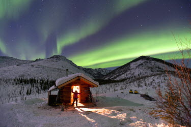 US02HRO0675 A person stands in the doorway of the Caribou Bluff cabin and watches the Northern Lights, White Mountain National Recreation Area north of Fairbanks Alaska, USA (MR)