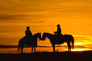 US51TEG0033 USA, Wyoming, Shell, Cowboys on ridge at Sunset. (MR)