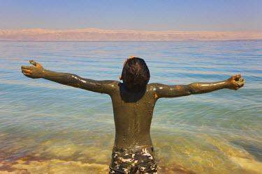 AS16KSU0004 Boy covered in mud in Dead Sea, Jordan. (MR)