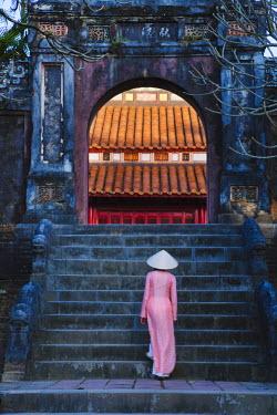 AS38KSU0299 Girl in Ao Dai (traditional Vietnamese long dress) and conical hat at Minh Mang Tomb, Hue, Thua Thien-Hue, Vietnam