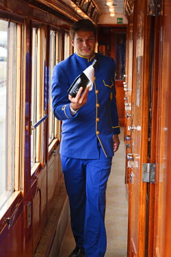 ITA1402 A steward on the Venice Simplon Orient Express train, bringing champagne to guests on board, Italy