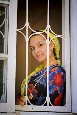 AR4367900032 Tejen, Ahal, Turkmenistan: A Young Woman'S Face Is Framed By Bars In A  Window Frame As She Is Looking Out From Her Home On 17Th June 2011,  Tejen,  Turkmenistan.