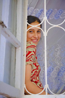 AR4367900033 Tejen, Ahal, Turkmenistan: A Young Woman'S Face Is Framed By Bars In A  Window Frame As She Is Looking Out From Her Home On 17Th June 2011,  Tejen,  Turkmenistan.