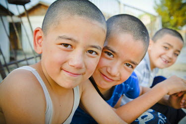 AR4367900038 Zahmet, Mari, Turkmenistan: Three Cheeky Boys Are Smiling While Sitting On The Footpath In The Late Evening On 20Th June 2011,  Zahmet,  Turkmenistan. Their Heads Are Shaved To Help Keep Them Cool In...