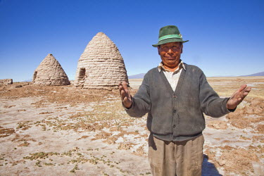 AR4521700010 Chipaya, Bolivia : A Portrait Of A Man In Farmer's Clothes As He Stands In Front Of Old burial sites In A Desert Scene.