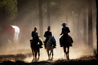 SPA4725 Huelva, Southern Spain. Horse riders passing through the forest on their way to the village of El Rocio during the annaul Romeria